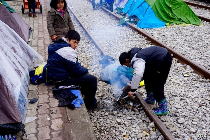 Children along tracks that lead to Macedonian boarder attempt to light fire to stay warm, in Idomeni, Greece, March 16, 2016. (J. Dettmer/VOA)