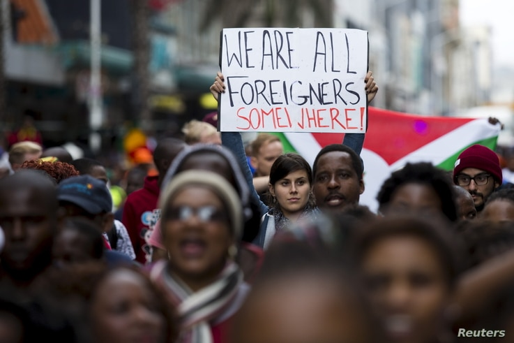 """A woman holds up a sign reading """"We are all foreigners somewhere!"""" during a peace march after anti-immigrant violence flared in Durban, April 16, 2015."""