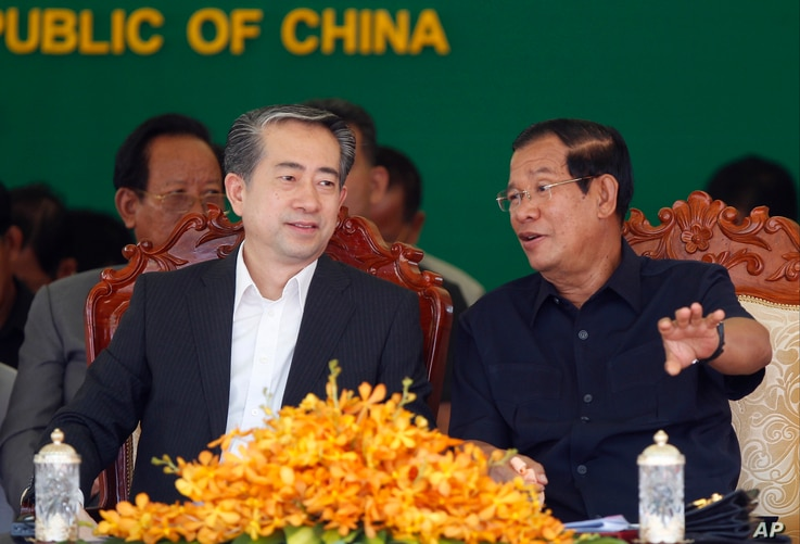 Cambodian Prime Minister Hun Sen, right, talks with Chinese Ambassador to Cambodia Xiong Bo, front left, during an inauguration ceremony of a sky bridge funded by China in Phnom Penh, Cambodia, July 2, 2018.