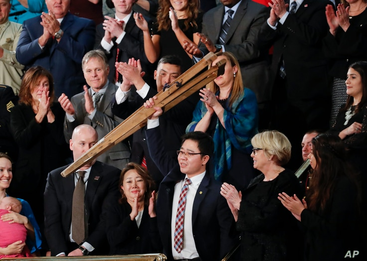Ji Seong-ho holds up his crutches after being acknowledged by President Donald Trump during Trump's address to a joint session of Congress on Capitol Hill in Washington, Jan. 30, 2018.