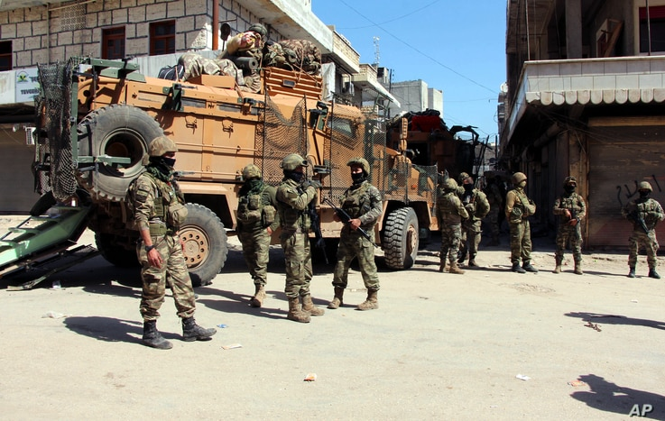 Turkish soldiers, positioned in the city center of Afrin, northwestern Syria, March 19, 2018, a day after they took the control of the area. Turkey's President Recep Tayyip Erdogan said following the victory in Syria's Afrin region, his country will ...