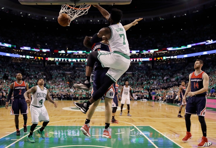 Boston Celtics forward Jaylen Brown (7) dunks over Washington Wizards guard Bojan Bogdanovic during the fourth quarter of Game 7 of a second-round NBA basketball playoff series, May 15, 2017, in Boston.