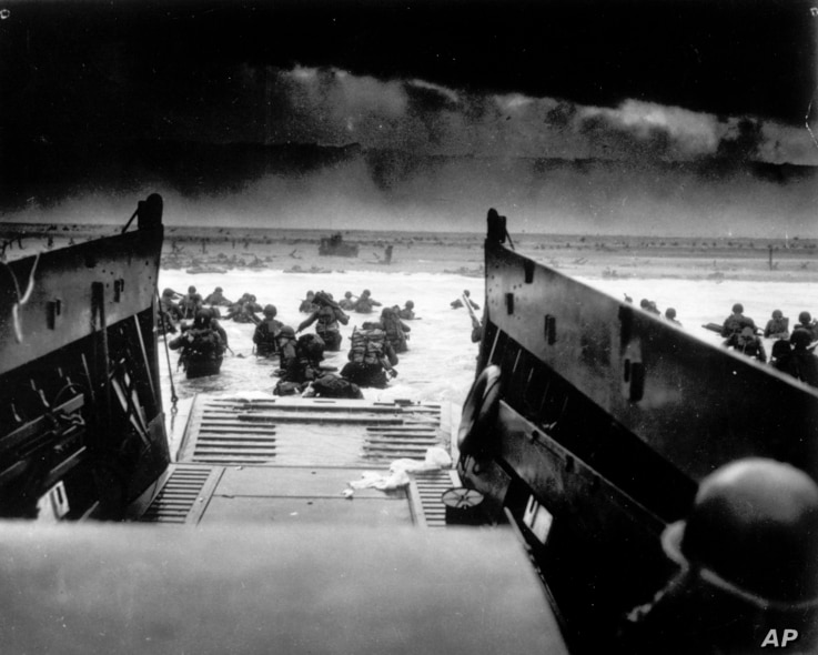 While under attack of heavy machine gun fire from the German coastal defense forces, these American soldiers wade ashore off the ramp of a U.S. Coast Guard landing craft, June 6, 1944, during the Allied landing operations at the Normandy. (AP Photo)