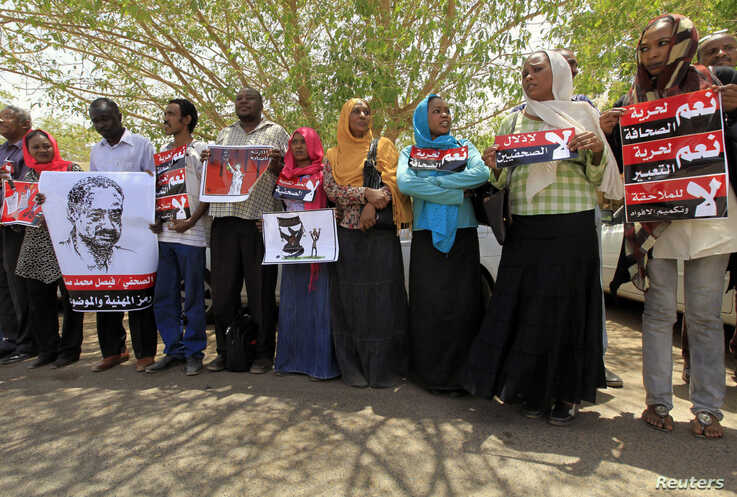 Journalists carry signs demanding freedom of press and expression during a demonstration against the violations of the security services towards the press and journalists outside the Council of the Press and Publication, in Khartoum, Sudan, May 16, 2