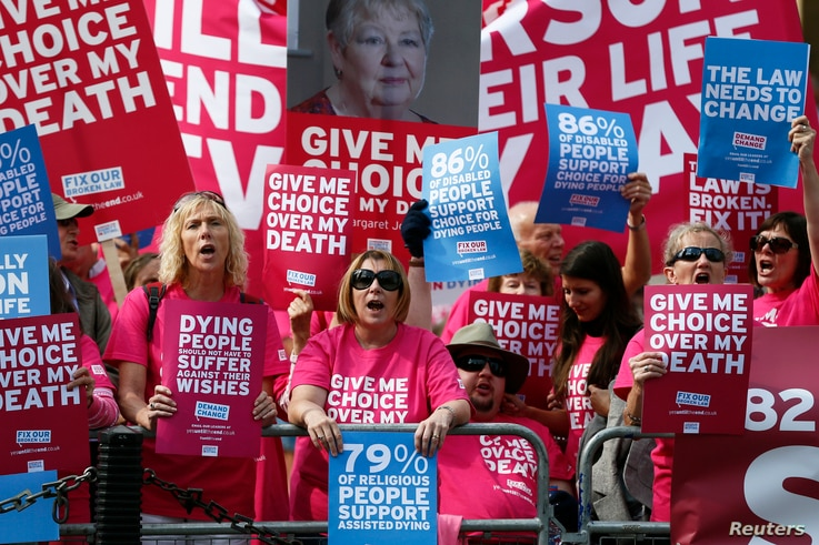 FILE - Campaigners in support of assisted dying protest outside the Houses of Parliament in central London, Sept. 11, 2015. The House of Commons rejected an assisted-dying bill that year, and the practice remains illegal today in Britain.