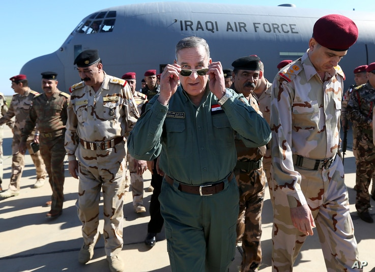 Iraqi Defense Minister Khaled al-Obeidi, center, arrives at a military a base outside Tikrit, 130 kilometers (80 miles) north of Baghdad, Iraq, March 9, 2016.