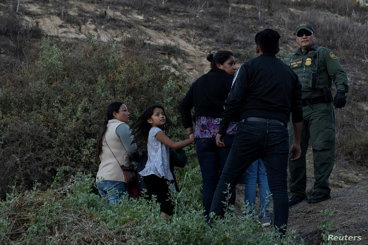 Migrants, part of a caravan of thousands from Central America trying to reach the United States, stand next to a U.S. Customs and Border Protection official in San Diego County, after crossing illegally from Mexico, Dec. 2, 2018.