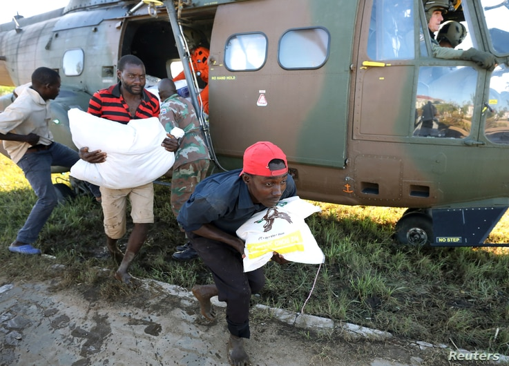 Workers offload food aid from a helicopter in the aftermath of Cyclone Idai, in Buzi, Mozambique, March 25, 2019.