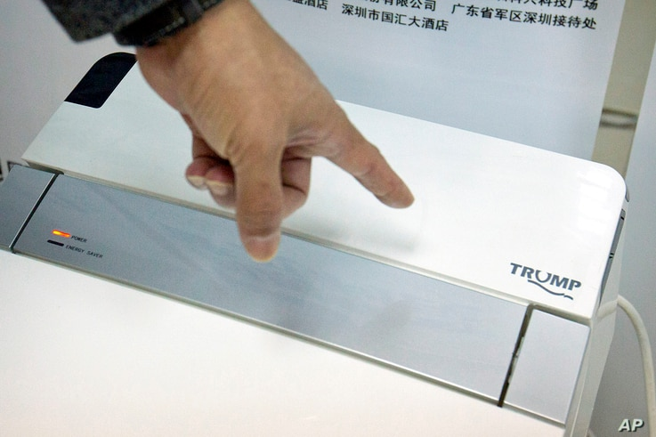 Zhong Jiye, a co-founder of Shenzhen Trump Industrial Co., points to the logo on one of his firm's high-end Trump-branded toilets at the company's offices in Shenzhen in southern China's Guangdong Province, Feb. 13, 2017.