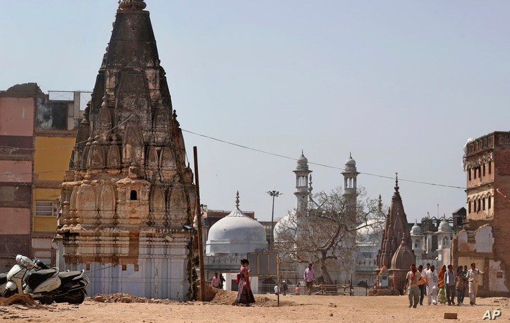 The 17th-century Gyanvapi mosque, the white structure sandwiched between Hindu temples, is seen in the background, March 19, 2019, as Hindu devotees walk at the site of a proposed grand promenade connecting the sacred Ganges river with a centuries-ol...