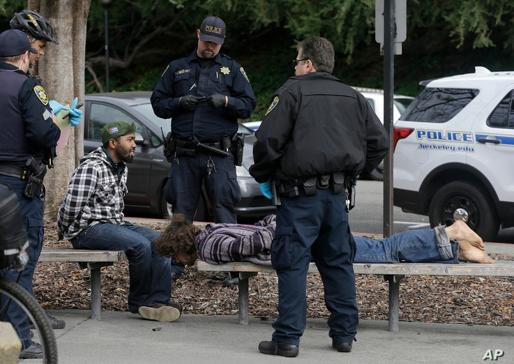 Police officers arrest two men who attacked a student on the University of California, Berkeley campus in Berkeley, Calif., Feb. 2, 2017.