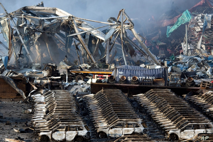 Charred remains of a warehouse and new cars are left burned after an explosion at a warehouse in northeastern China's Tianjin municipality, Aug. 13, 2015.