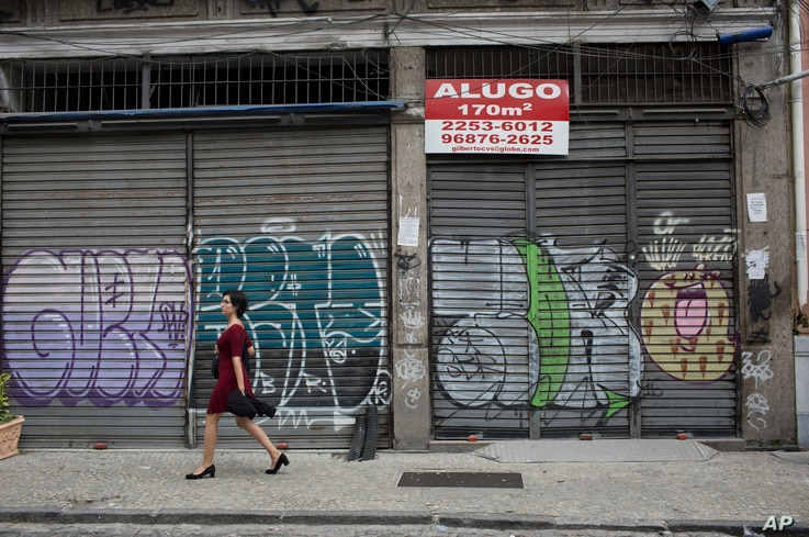 """In this May 31, 2017 photo, stores stand shuttered in downtown Rio de Janeiro, Brazil. The sign reads """"Rent"""" in Portuguese."""