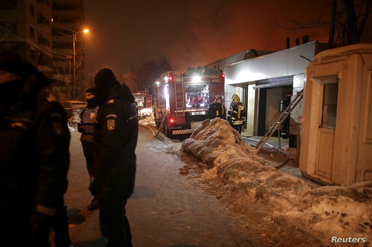 Romanian gendarmes cordon off a part of a street as firefighters work at the scene of a blaze that destroyed a night club in Bucharest, Romania, Jan. 21, 2017.