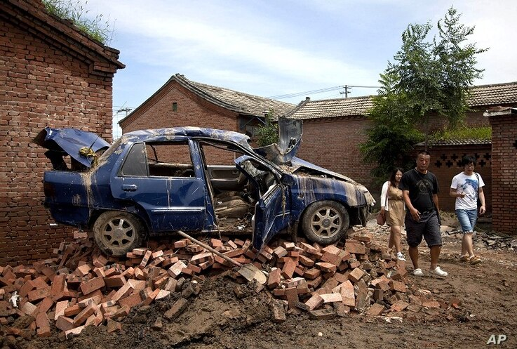 Chinese people walk past a flood-damaged vehicle sitting on the bricks at a village in Fangshan district of Beijing, China, July 23, 2012.