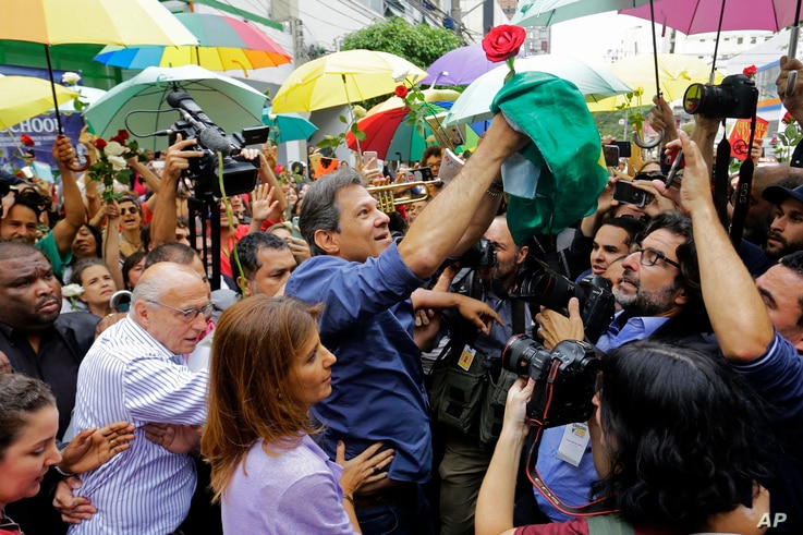 Workers' Party presidential candidate Fernando Haddad holds a Brazilian flag after casting his vote in the presidential election in Sao Paulo, Brazil, Sunday, Oct. 28, 2018.