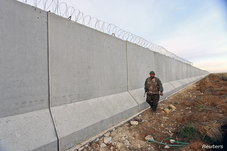 A Kurdish People's Protection Units (YPG) fighter walks near a wall, which activists said was put up by Turkish authorities, on the Syria-Turkish border in the western countryside of Ras al-Ain, Syria, Jan. 29, 2016.