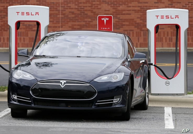 A Telsa car recharges at a Tesla charging station in Charlotte, North Carolina, Saturday, June 24, 2017.