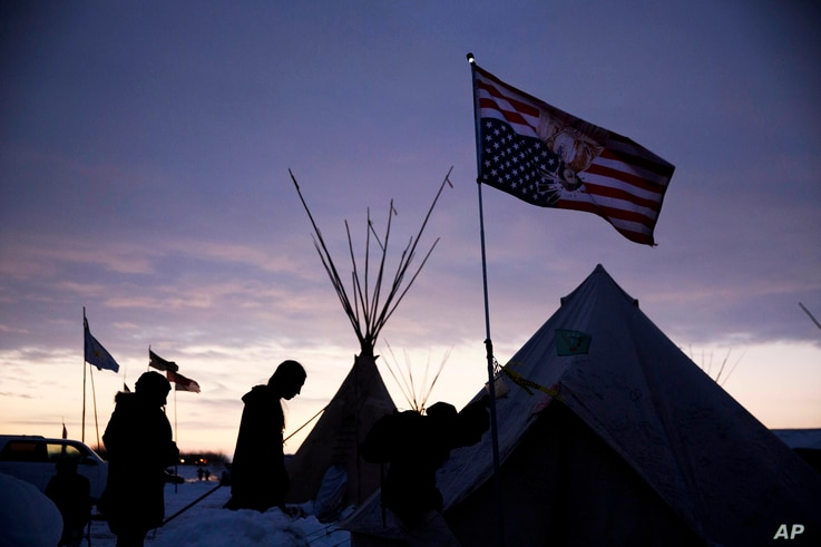 FILE - Travelers arrive at the Oceti Sakowin camp where people have gathered to protest the Dakota Access oil pipeline as they walk into a tent next to an upside-down American flag in Cannon Ball, North Dakota, Dec. 2, 2016.