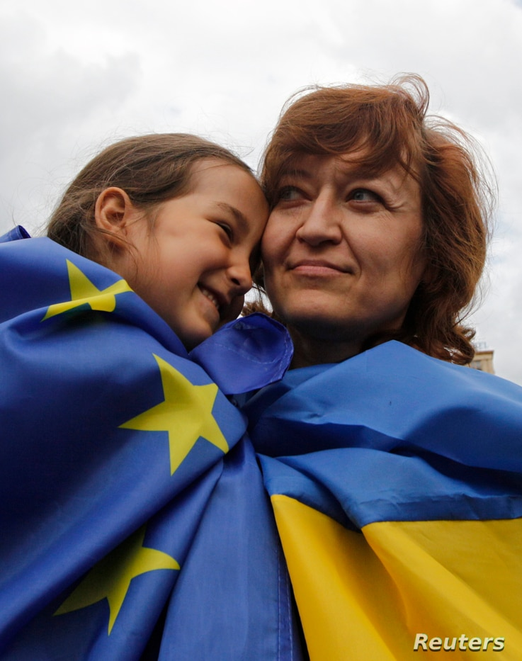 A girl and woman, respective draped in European Union and Ukrainian national flags, celebrate in Independence Square in Kyiv June 27, 2014.