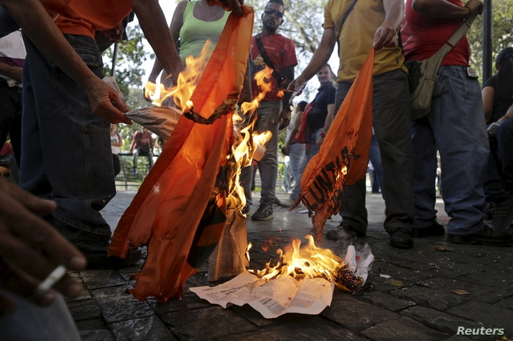 Supporters of Venezuela's President Nicolas Maduro burn a flag of the opposition party Popular Will (Voluntad Popular) close to the National Assembly in Caracas, Jan. 5, 2016.