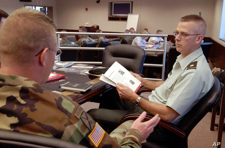 FILE - Major Jeff Jennings, right, talks with Captain Joseph Scanlin before the start of a talk by writer McKay Jenkins during a workshop sponsored by the National Endowment for the Arts at the 10th Mountain Division in Fort Drum, N.Y., June 5, 2004....