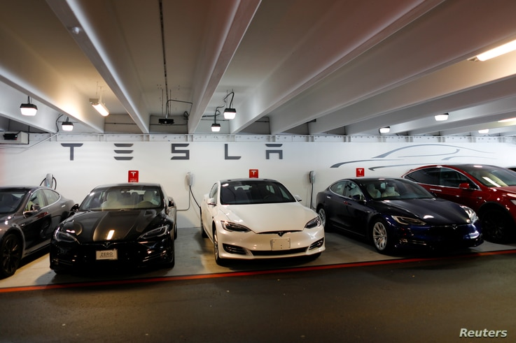 FILE - Tesla Model 3s and X's are shown charging in an underground parking lot next to a Tesla store in San Diego,California, U.S., May 30, 2018.