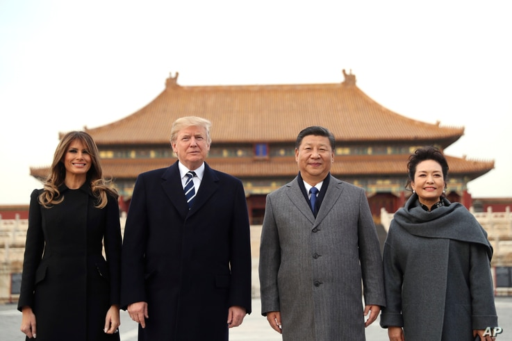 President Donald Trump, second left, first lady Melania Trump, left,  Chinese President Xi Jinping, second right, and his wife Peng Liyuan, right, stand together as they tour the Forbidden City, Nov. 8, 2017, in Beijing, China.