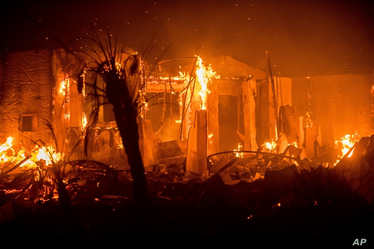 Flames consume a structure as the Lilac fire burns in Bonsai, Calif., Dec. 8, 2017.