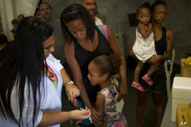 Tais da Silva Almeida comforts her 5-year-old daughter as a health worker prepares to inject her with a yellow fever vaccine in a field hospital in Casimiro de Abreu, Brazil, March 17, 2017.