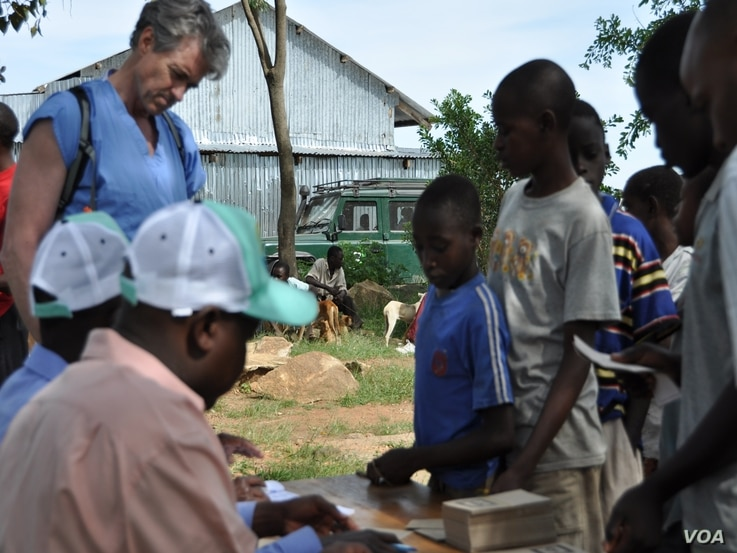 Children in Tanzania register their dogs for rabies vaccination.