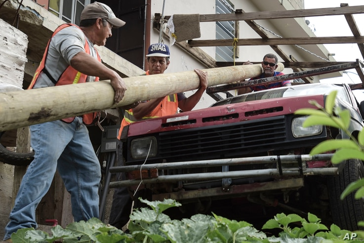 Retired carpenter Felipe Rodriguez, far right, uses his truck to help municipal workers, who are also locals, Eliezer Nazario, left, and Tomas Martinez, move an electric post so they can install it near his home, Jan. 31, 2018, four months after Hurr...