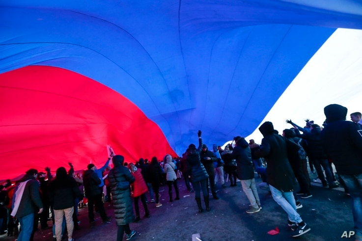 People hold a huge Russian flag during a rally to celebrate the second anniversary of Russia's annexation of Crimea just off Red Square in Moscow, Russia, March 18, 2016.