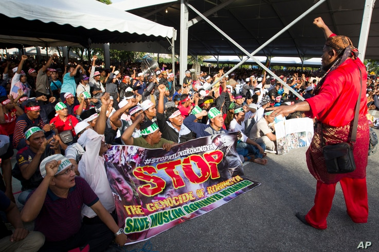 Myanmar ethnic Rohingya Muslims raise clenched fists during a protest against the persecution of Rohingya Muslims in Myanmar, in Kuala Lumpur, Malaysia, Dec. 4, 2016.