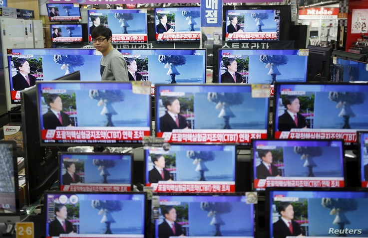 A sales assistant in Seoul, South Korea, watches TV sets broadcasting a news report on North Korea's nuclear test, Jan. 6, 2016.