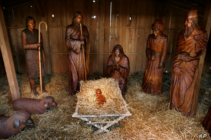 FILE - Carved wooden figures populate the Nativity scene on the Arkansas state Capitol grounds in Little Rock, Dec. 17, 2007.