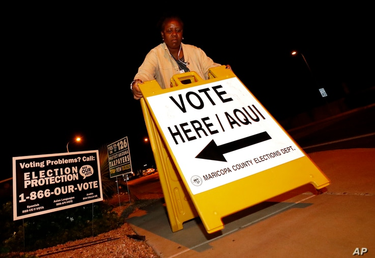 "Maricopa County elections official Deborah Atkins places a ""vote"" sign outside a polling station prior to its opening, Nov. 6, 2018, in Phoenix."