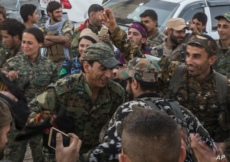 """Members of the U.S.-backed Syrian Democratic Forces (SDF) dance a traditional Syrian """"Dabka"""" as they celebrate in front of stadium that was the site of Islamic State fighters' last stand in the city of Raqqa, Syria, Friday, Oct. 20, 2017."""