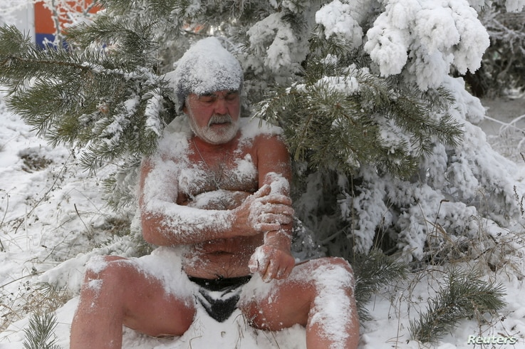 Nikolai Bocharov, 77, a member of the Cryophile winter swimmers club, rubs snow on his body as he sits on a snowdrift after bathing in the icy water of the Yenisei River in the Siberian city of Krasnoyarsk, Russia, Nov. 21, 2015.