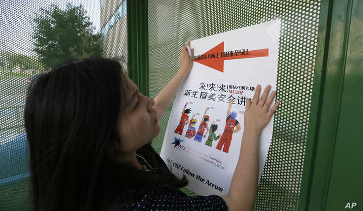 FILE - Ailu Xu, a graduate student from China, posts a sign directing Chinese students to new student orientation at the University of Texas at Dallas in Richardson, Texas, Aug. 22, 2015.