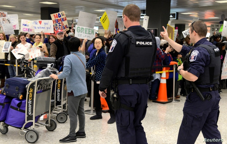 Police direct arriving passengers past dozens of pro-immigration demonstrators who cheer and hold signs at Dulles International Airport, to protest President Donald Trump's travel ban in Chantilly, Virginia, in suburban Washington, U.S., Jan. 29, 201...