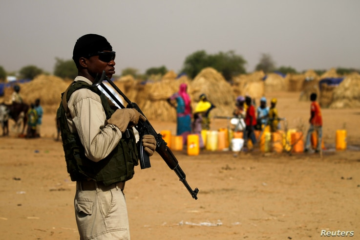 FILE - A Nigerien soldier stands guard in a camp of the city of Diffa during the visit of Niger's Interior Minister Mohamed Bazoum following attacks by Boko Haram fighters in the region of Diffa, June 18,2016.