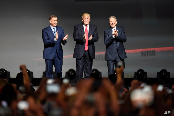 FILE - President Donald Trump stands with National Rifle Association Executive Vice President Wayne LaPierre, right, and Chris W. Cox, executive director of the National Rifle Association Institute for Legislative Action as he arrives for the Nationa...