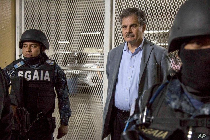 Juan Alberto Fuentes, former Guatemalan Minister of Finance and currently chair of the NGO Oxfam International, is flanked by police as they wait to enter a holding cell in a courthouse, in Guatemala City, Tuesday, Feb. 13, 2018.