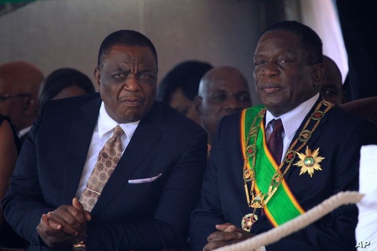 Zimbabwean President Emmerson Mnangagwa right, sits with his Deputy Constantino Chiwenga during a Heroes' Day event to commemorate the lives of those who died in the southern African country's 1970s war against white minority rule, in Harare, Aug. 13...