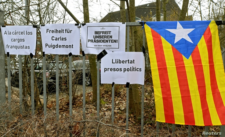 """An Estelada (Catalan separatist flag) is seen next to slogans in front of the prison in Neumuenster, Germany, March 26, 2018. The signs read """"Freedom for Carles Puigdemont,"""" """"Free Our President"""" and """"Free Political Prisoners."""""""
