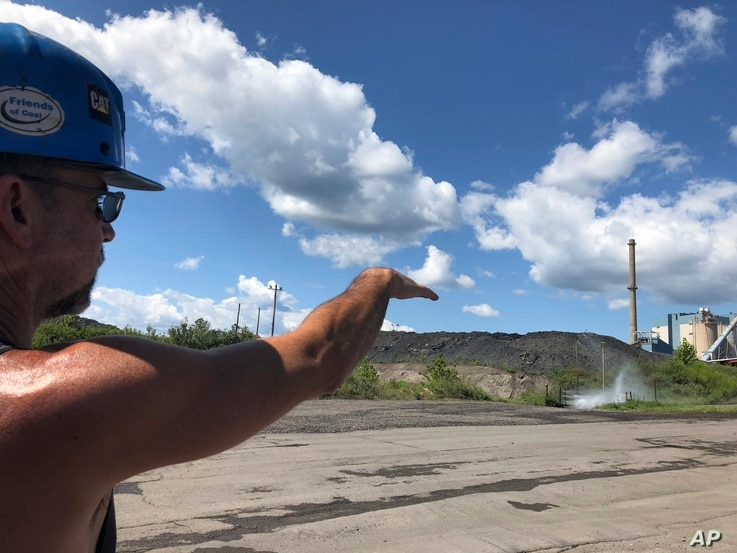 Brian Weekly, a contractor at West Virginia's Grant Town coal-fired power plant, gestures toward the small facility's smokestack,  Aug. 23, 2018 in Grant Town.