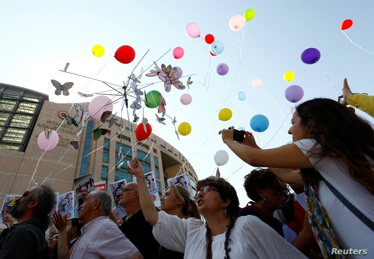 Journalists and press freedom activists release balloons during a demonstration in solidarity with the members of the opposition newspaper Cumhuriyet who were accused of supporting a terrorist group outside a courthouse, in Istanbul, Turkey, July 24,...