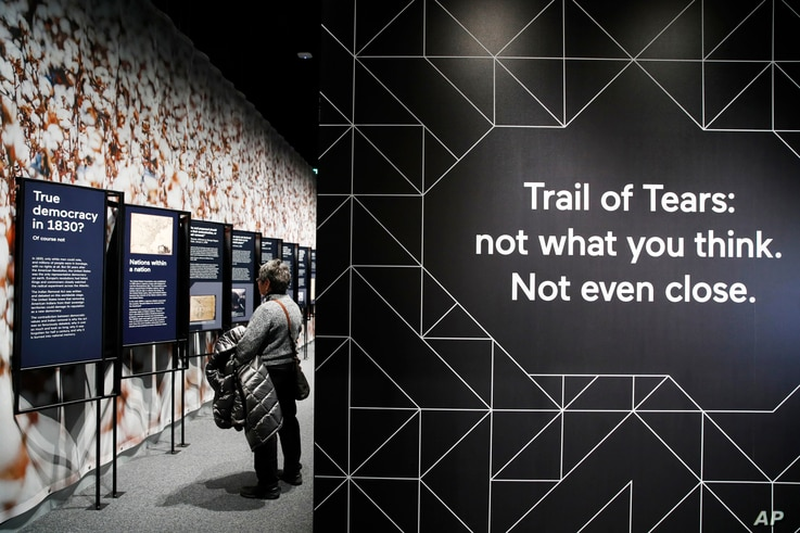 """FILE - A woman looks at a section of the """"Americans"""" exhibit that explores the historical context of the Trail of Tears, at the Smithsonian's National Museum of the American Indian in Washington, Feb. 9, 2018."""
