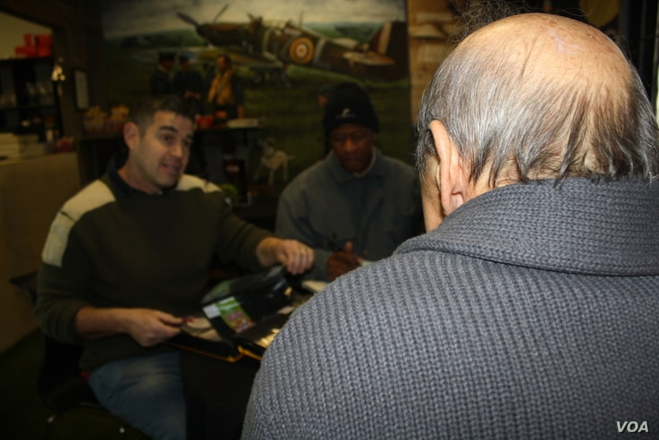 Alan Coleman speaks with a war veteran who has brought him medals and badges to evaluate. (D. Taylor/VOA)